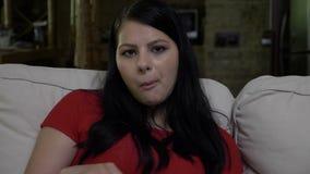 沮丧的妇女在破坏以后坐长沙发并且吃玉米花 股票视频