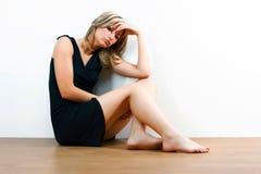 年轻沮丧的妇女坐地板 免版税图库摄影
