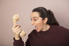沮丧的妇女尖叫对电话 库存图片