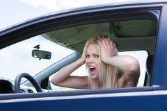 沮丧的妇女尖叫的坐在汽车 库存照片