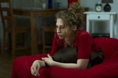 沮丧的妇女抽烟的香烟 库存图片