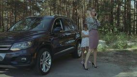沮丧的妇女要求协助在残破的汽车附近 影视素材