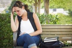沮丧的害怕的少妇坐长凳在公园 免版税图库摄影