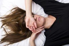 沮丧的少妇在她的床上在,盖她的眼睛 库存图片