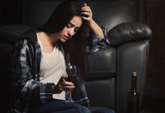 沮丧的少妇饮用的酒 免版税库存图片