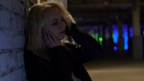 沮丧的白肤金发的妇女遭受头疼的,站立的单独外部夜总会 股票视频