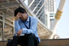 沮丧的被注重的亚洲商人用在前额的手坐楼梯在城市 浓缩沮丧的失业的事务 免版税库存图片