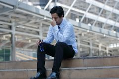 沮丧的被注重的年轻亚洲商人感觉疲倦和用尽与他的工作 库存照片
