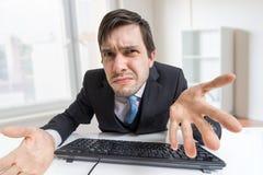 沮丧的迷茫和缺乏信心的人与计算机一起使用在办公室 免版税库存照片