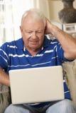 沮丧的退休的老人在家坐沙发使用膝上型计算机 库存图片