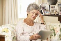 沮丧的退休的资深妇女在家坐沙发使用数字式片剂 免版税库存图片