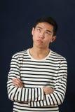 沮丧的年轻亚裔人用卷起眼睛的横渡的手 库存图片