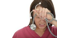 沮丧的年轻女性医生的被注重的联邦机关有听诊器的 免版税库存图片