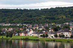 河、房子、森林和天空 库存照片