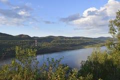 河、树木繁茂的小山和导线的看法在河 免版税库存照片