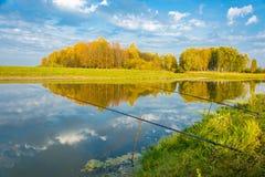 河与钓鱼竿的秋天风景 免版税库存图片