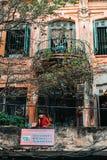 河内,越南,12 20 18:在街道的生活在河内 一个阳台的老妇人一古老buidling的 图库摄影