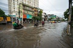 河内,越南- 2017年7月17日:交易在被充斥的Minh Khai街道上在与汽车,横渡深水的摩托车的大雨以后 库存照片