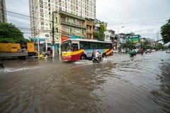 河内,越南- 2017年7月17日:交易在被充斥的Minh Khai街道上在与汽车,横渡深水的摩托车的大雨以后 库存图片