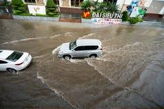 河内,越南- 2017年7月17日:交易在被充斥的Minh Khai街道上在与汽车,横渡深水的摩托车的大雨以后 免版税库存图片