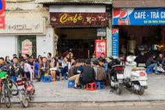 河内,越南- 2015年3月15日:人们喝在咖啡馆摊位的咖啡、茶或者汁液果子在Nha Tho街道, Hano的中心的边路 图库摄影