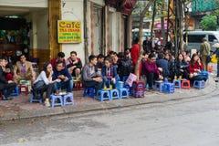 河内,越南- 2015年3月15日:人们喝在咖啡馆摊位的咖啡、茶或者汁液果子在Nha Tho街道, Hano的中心的边路 库存照片