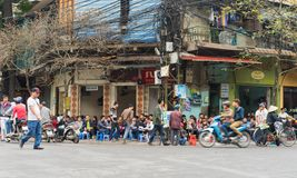 河内,越南- 2015年3月15日:人们喝在咖啡馆摊位的咖啡、茶或者汁液果子在Nha Tho街道, Hano的中心的边路 免版税图库摄影