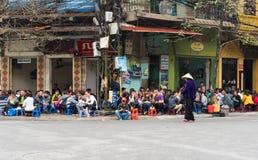 河内,越南- 2015年3月15日:人们喝在咖啡馆摊位的咖啡、茶或者汁液果子在Nha Tho街道, Hano的中心的边路 库存图片
