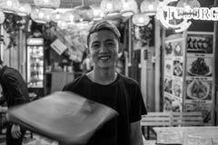 河内,越南- 2018年4月17日:侍者转动菜单并且对在河内的Bia Hoi角落的照相机微笑 免版税库存照片