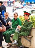 河内,越南- 2016年12月16日:制服的年长人在城市停放 特写镜头 垂直 免版税库存图片