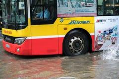 河内,越南- 2017年7月17日:在大雨以后的被充斥的Minh Khai街道与横渡深水的公共汽车 库存照片