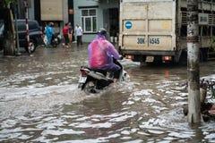 河内,越南- 2017年7月17日:在大雨以后的被充斥的Minh Khai街道与横渡深水的摩托车和汽车在河内c 免版税库存图片