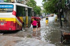 河内,越南- 2017年7月17日:在大雨以后的被充斥的Minh Khai街道与横渡深水的汽车和人 库存照片