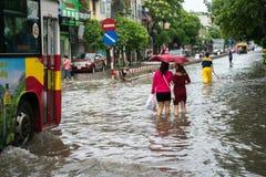 河内,越南- 2017年7月17日:在大雨以后的被充斥的Minh Khai街道与横渡深水的汽车和人 图库摄影