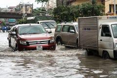 河内,越南- 2017年7月17日:在大雨以后的被充斥的Minh Khai街道与横渡深水的汽车和摩托车 免版税库存照片