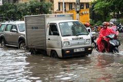河内,越南- 2017年7月17日:在大雨以后的被充斥的Minh Khai街道与横渡深水的汽车和摩托车 免版税库存图片
