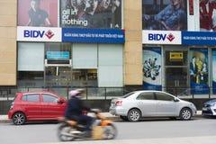 河内,越南- 2014年11月9日:在Ba Trieu街道的Vincom大厦有束的BIDV银行商标 包装在街道边和mot的汽车 免版税库存图片