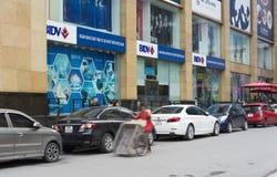 河内,越南- 2014年11月9日:在Ba Trieu街道的Vincom大厦有束的BIDV银行商标 包装在街道边和mot的汽车 库存照片