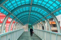 河内,越南- 2015年3月15日:在Xa丹街道的走道桥梁里面,河内 走在桥梁的一个老人 免版税图库摄影