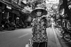 河内,越南- 2018年4月13日:女性摊贩步行沿着向下河内街道  免版税库存照片