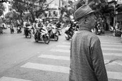 河内,越南- 2018年4月13日:年长人在河内观看强烈的交通 免版税库存图片