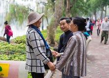 河内,越南- 2015年3月15日:愉快地看见他们的朋友的夫妇在Hoan Kiem湖, Hoan Kiem区 握手的妇女 库存图片