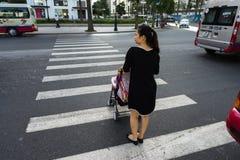 河内,越南- 2016年10月19日:有穿过街道的婴儿车的母亲在Minh Khai 运行在街道上的车 免版税库存图片