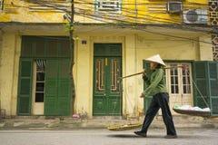 河内,越南- 2014年4月13日:未认出的供营商回家与在老房子的空的篮子河内str的,越南 库存图片