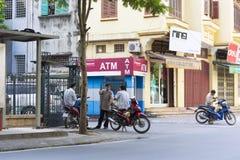 河内,越南- 2014年9月14日:未认出的小组出租汽车摩托车司机谈话在Hoa Lu街道上的ATM前面 免版税库存图片