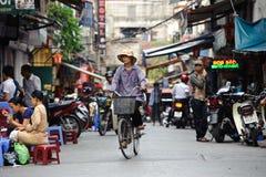 河内,越南- 2010年10月14日:未认出的越南妇女在河内街道骑自行车  免版税库存照片