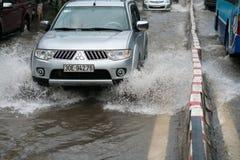 河内,越南- 2017年7月17日:汽车通过一个大水坑飞溅在被充斥的街道在大雨以后在Minh Khai,河内 免版税库存图片