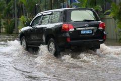 河内,越南- 2017年7月17日:汽车通过一个大水坑飞溅在被充斥的街道在大雨以后在Minh Khai,河内 免版税库存照片