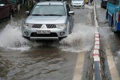 河内,越南- 2017年7月17日:汽车通过一个大水坑飞溅在被充斥的街道在大雨以后在Minh Khai,河内 免版税图库摄影