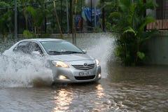 河内,越南- 2017年7月17日:汽车通过一个大水坑飞溅在被充斥的街道在大雨以后在Minh Khai,河内 库存照片